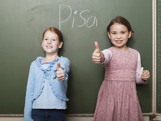 Mädchen steht an der Tafel in der Schule