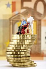 Figur im Rollstuhl und Betreuer auf Stapel von Münzen