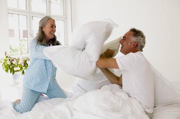 Älteres Paar bei Kissenschlacht auf dem Bett