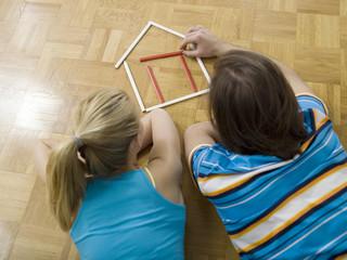 Paar auf dem Boden liegend, baut Haus aus Stiften