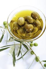 Frische grüne Oliven und Olivenöl in Glasschale
