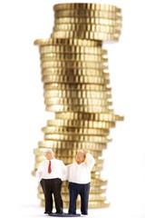 Business-Figuren und Stapel von Münzen