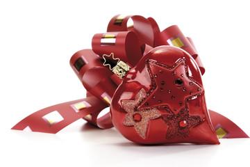 Rotes Geschenkband mit herzförmigem Christbaumschmuck