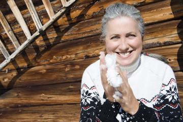 Italien, Südtirol, Seiseralm,Seniorin hält Schnee in Händen, lächelnd, Porträt