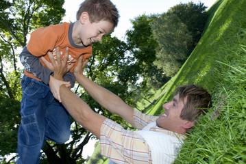 Vater liegt im Gras und hält Sohn, lächelnd