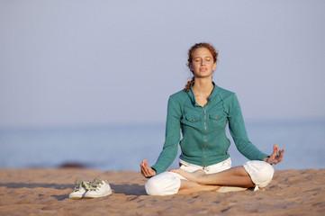 Junge Frau meditiert am Strand