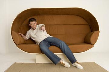 Junger Mann sitzt auf dem Sofa, mit Fernbedienung