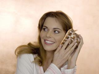 Frau hält Muschel ans Ohr, lächelnd, Nahaufnahme