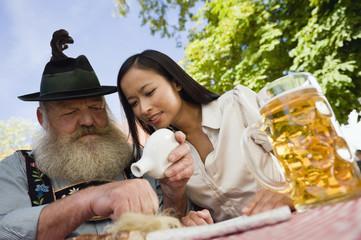 Deutschland, Bayern, Oberbayern, Bayer und asiatische Frau im Biergarten, Schnupftabak
