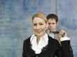 Geschäftsfrau zieht an Krawatte des Kollegen