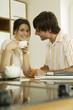 Junges Paar trinkt Tee in der Küche, Lächeln, Portrait