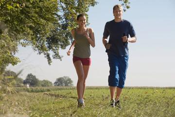 Junges Paar, Joggen im Feld