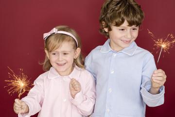 Junge und Mädchen mit Wunderkerzen, lächelnd