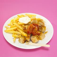 Currywurst und Pommes mit Sauce in Teller, Nahaufnahme