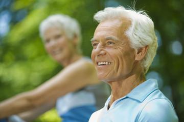 Älterer Mann der lächelt, Frau im Hintergrund, Porträt