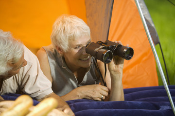 Älteres Paar beim Camping, Frau mit Feldstecher, Portrait