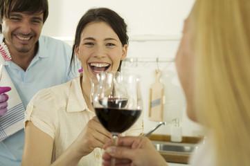 Drei junge Leute trinken Wein in der Küche, Lächeln, Nahaufnahme