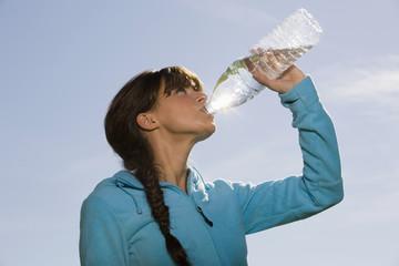 Junge Frau trinkt Wasser aus Flasche