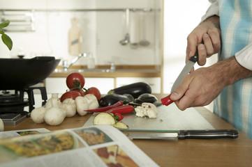 Junger Mann schneidet Gemüse in der Küche, Nahaufnahme