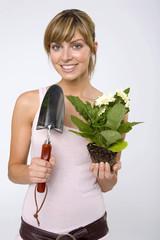 Junge Frau mit Topfpflanze und Kelle, lächelnd, Nahaufnahme