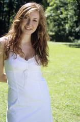 Junge Frau im weißen Kleid steht im Garten, Lächeln, Portrait