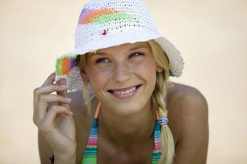 Junge Frau am Strand mit Sonnenhut, Nahaufnahme