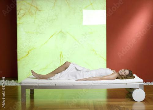 Frau liegt auf der Couch, lächelnd