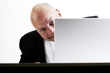 Mann schaut hinter Laptop hervor