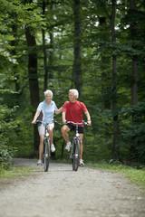 Älteres Paar, Radfahren auf Waldweg