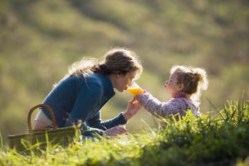 Mutter mit Tochter sitzend auf der Wiese