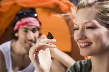 Deutschland, Bayern, Junges Paar beim Camping, Schmetterling auf der Hand