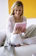 Frau auf Sofa, Blick auf Buch, lächelnd