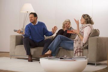 Eltern mit Tochter sitzen auf dem Sofa im Wohnzimmer