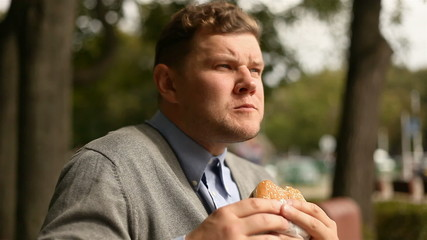 young businessman eating a hamburger