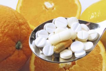 Vitaminpillen und Orangen