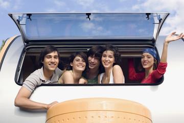 Junge Menschen schauen aus Campinganhänger, Lächeln, Portrait