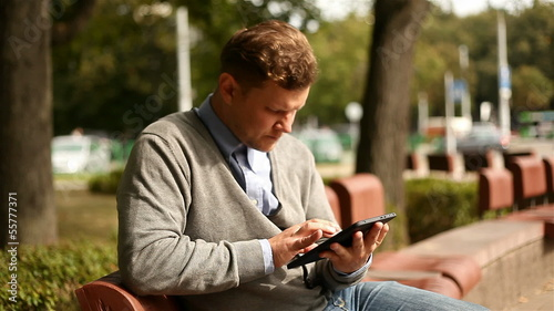 Young businessman working on tablet computer in city park, 1080p