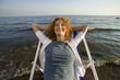 Junge Frau liegt entspannt im Liegestuhl am Strand, lächelnd, Nahaufnahme