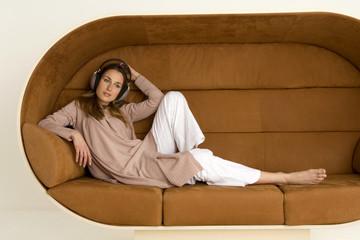 Junge Frau sitzt auf dem Sofa, Kopfhörer