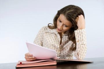 Junge Frau liest in Dokumenten, Kopf kratzend