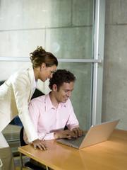 Mann und Frau im Büro, mit Laptop, lächelnd