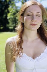 Junge Frau im weißen Kleid stehend im Garten, die Augen geschlossen, Nahaufnahme