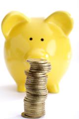 Stapel von Münzen mit gelbem Sparschwein