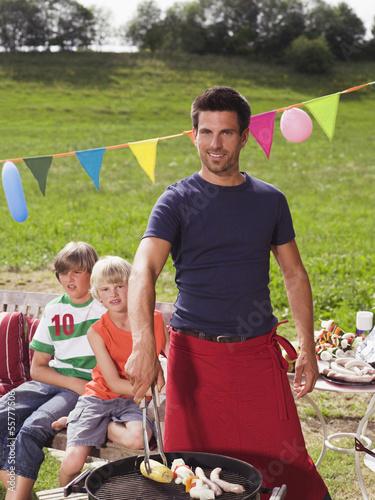 Vater der den Grill vorbereitet, Kinder im Hintergrund