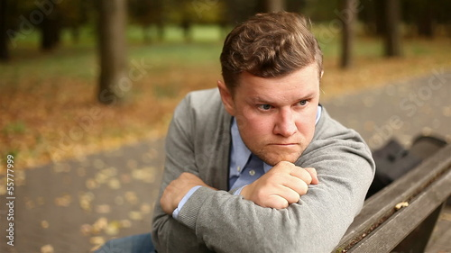 Depressed, sad young businessman sitting in the park, 1080p