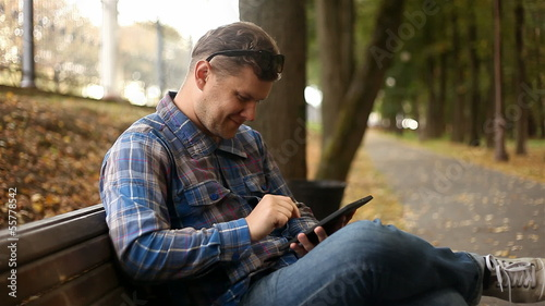 Young man working on tablet computer in city park, 1080p