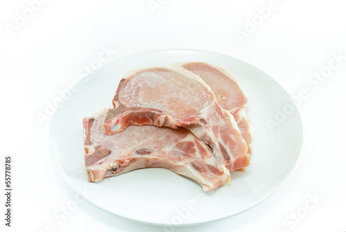 frozen meat ,pork chops ,on white plate