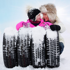 Mother and child with winter tyres in the snow