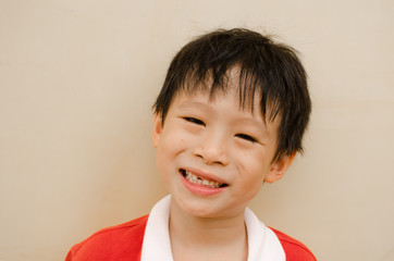 young boy smiles and shows his missing teeth