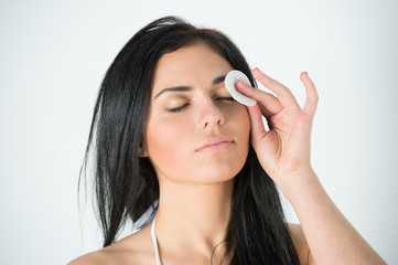 Woman cleaning face with cotton swab